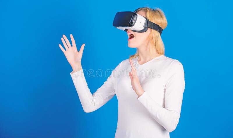 Vrolijke glimlachende vrouw die in VR-glazen kijken Zekere jonge vrouw die haar het virtuele werkelijkheid hoofdtelefoon en gliml stock afbeelding