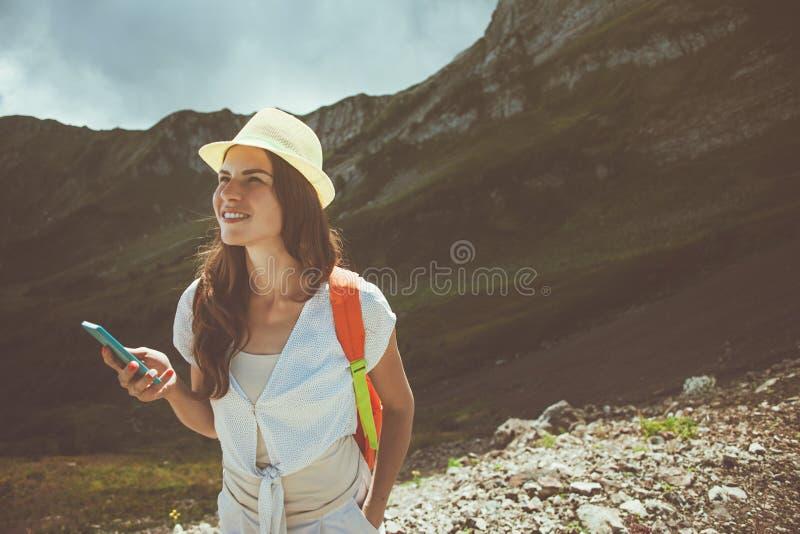 Vrolijke glimlachende vrouw met mobiele telefoon die in bergen reizen Mooie weiden toeristische weg Digitale mededeling stock fotografie