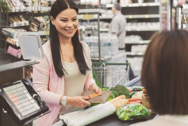 Vrolijke glimlachende vrouwelijke persoon die voor goederen gaan betalen stock afbeelding
