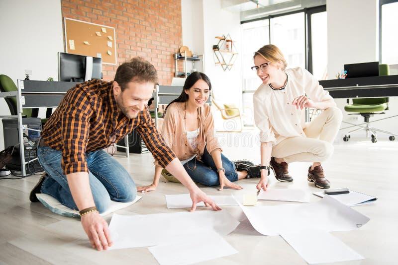 Vrolijke glimlachende werknemers die samenwerken stock afbeeldingen