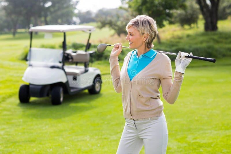 Vrolijke golfspeler die zich op groen zetten bevinden stock fotografie