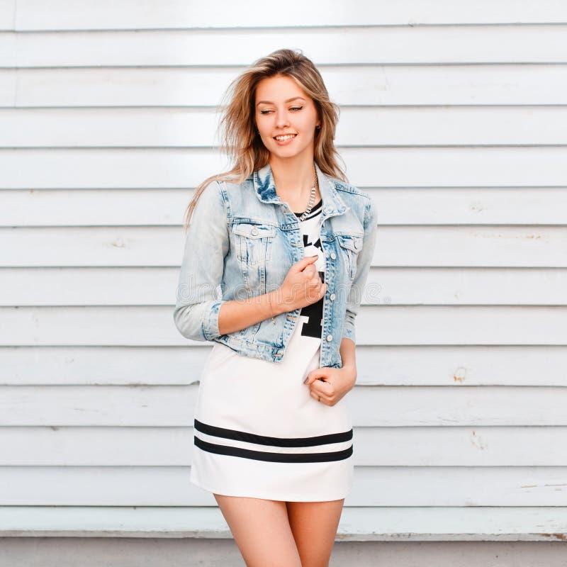 Vrolijke grappige jonge vrouw in Amerikaanse stijl dichtbij een wit blokhuis Het charmante meisje geniet van een warme zonnige da stock fotografie