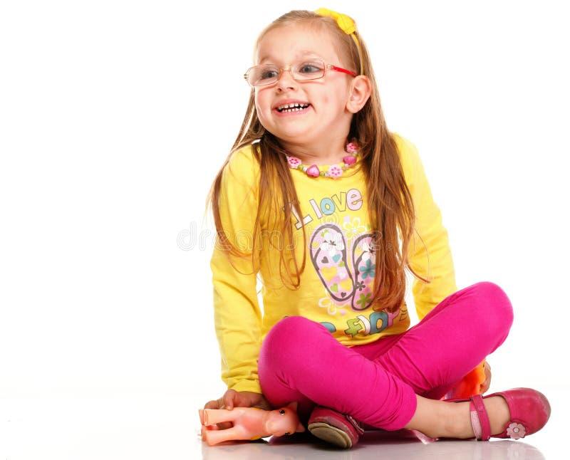 Vrolijke grappige meisjeglazen en geïsoleerdg stuk speelgoed stock fotografie