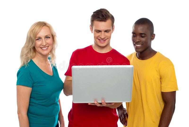 Vrolijke groep vrienden die aan laptop werken royalty-vrije stock foto