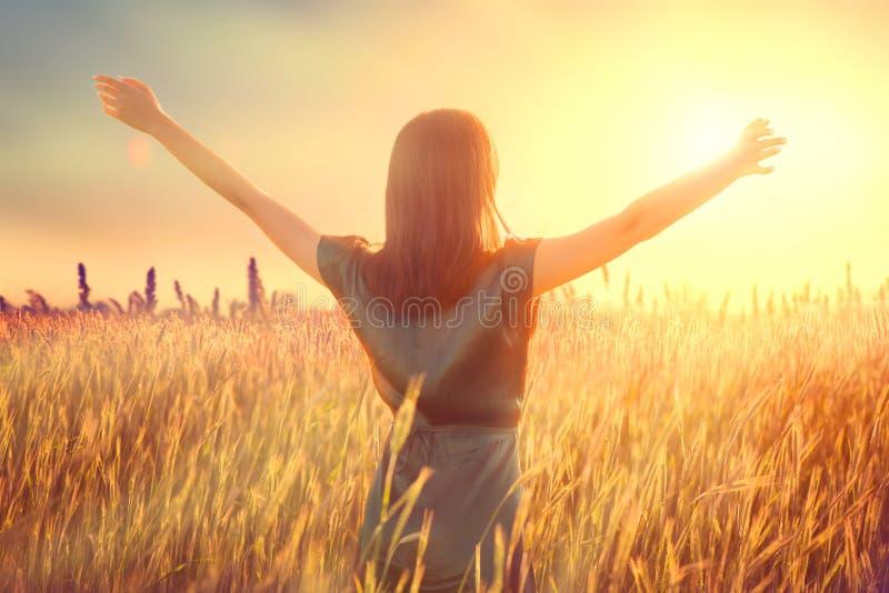 Vrolijke herfstvrouw die de hand over de zonsondergang opstak, geniet van leven en natuur Schoonheidsvrouwtje op het veld met zon royalty-vrije stock fotografie