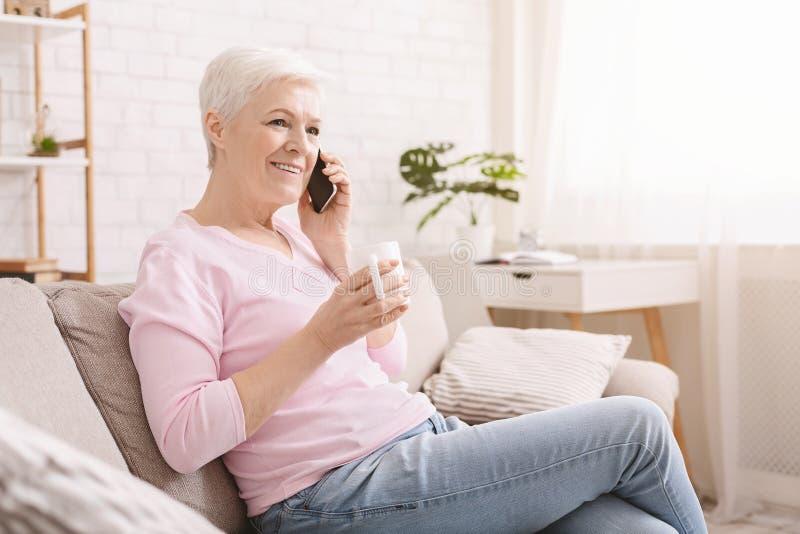 Vrolijke hogere dame die telefoongesprek op haar smartphone hebben stock afbeelding