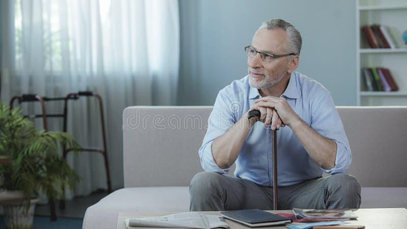 Vrolijke hogere mannelijke zitting op bank en het denken over terugwinning, rehabilitatie royalty-vrije stock foto's