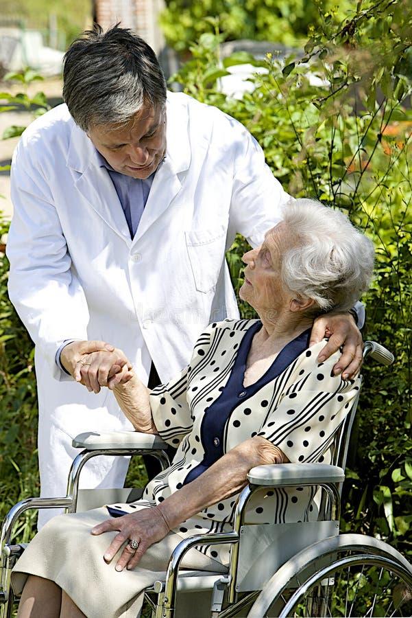 Vrolijke hogere patiënt in rolstoel met een vriendschappelijke buiten verzorger royalty-vrije stock fotografie