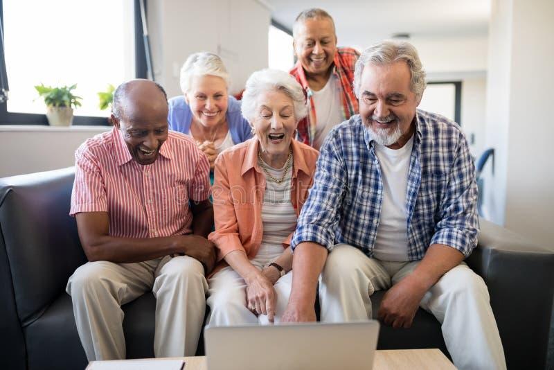 Vrolijke hogere vrienden die laptop op lijst bekijken royalty-vrije stock foto