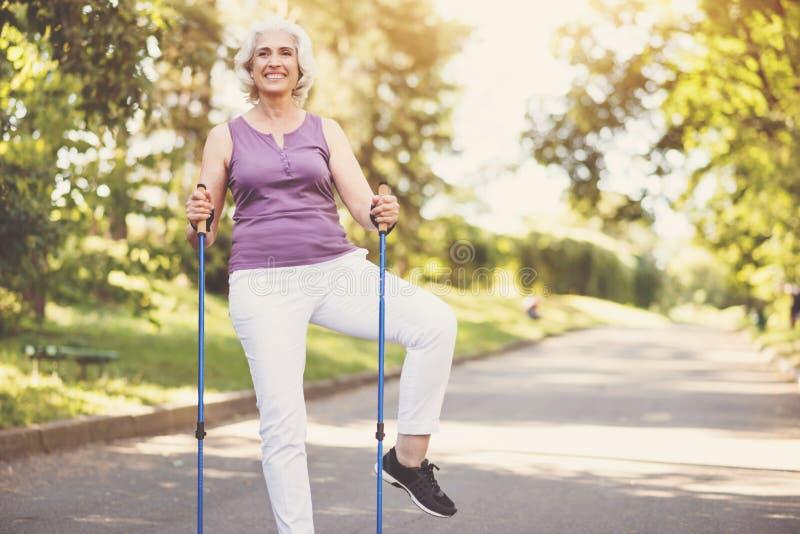 Vrolijke hogere vrouw die een lichaamsbeweging doen stock afbeelding