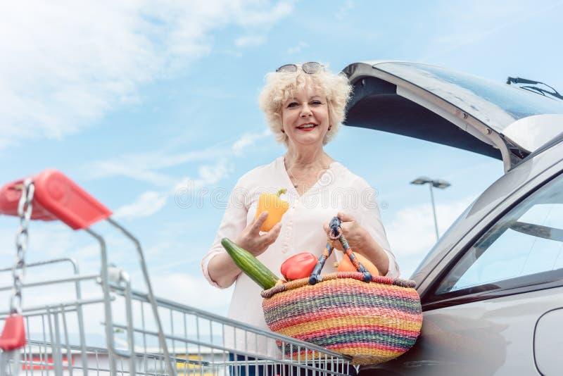 Vrolijke hogere vrouw die een mandhoogtepunt van verse groenten houden stock foto's