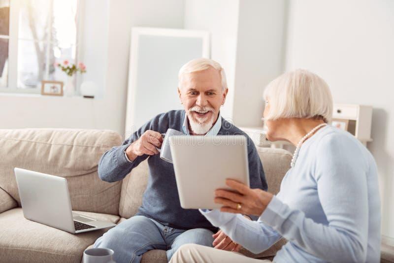 Vrolijke hogere vrouw die haar update van het echtgenootnieuws tonen stock afbeeldingen