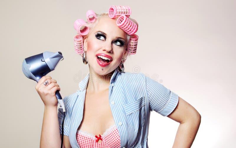 Vrolijke huisvrouw met hairdryer stock afbeelding