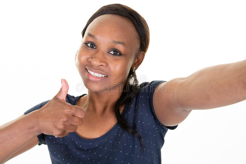 Vrolijke jonge Afrikaanse Amerikaanse vrouw die het mobiele telefoon selfie het glimlachen stellen op witte achtergrond gebruiken royalty-vrije stock foto