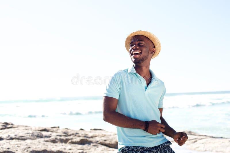 Vrolijke jonge Afrikaanse mens die bij het strand genieten van stock afbeelding