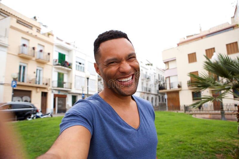 Vrolijke jonge Afrikaanse mens die selfie in openlucht in stad nemen royalty-vrije stock afbeeldingen