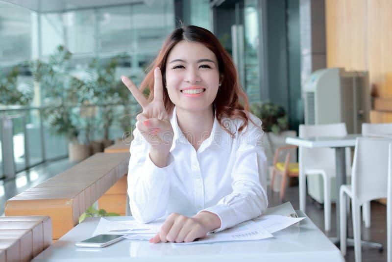 Vrolijke jonge Aziatische bedrijfsvrouw die vinger twee houden als teken zoals vechtend met baan op kantoor royalty-vrije stock foto