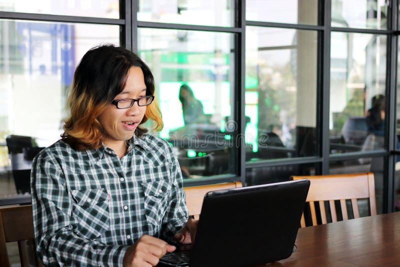 Vrolijke jonge Aziatische hipster met vrijetijdskleding die met laptop voor zijn baan in werkplaats van bureau werken stock foto