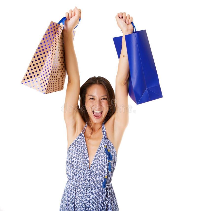 Vrolijke jonge Aziatische vrouw die het winkelen zakken steunen tegen geïsoleerde witte achtergrond royalty-vrije stock afbeelding