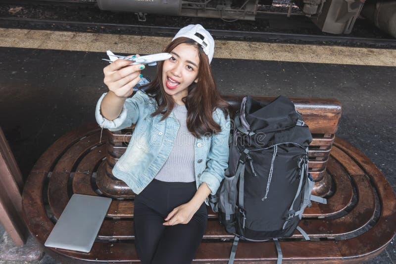 Vrolijke jonge Aziatische vrouwenreiziger met modeltreinzitting die op bank op het aankomen trein bij post wachten stock foto's