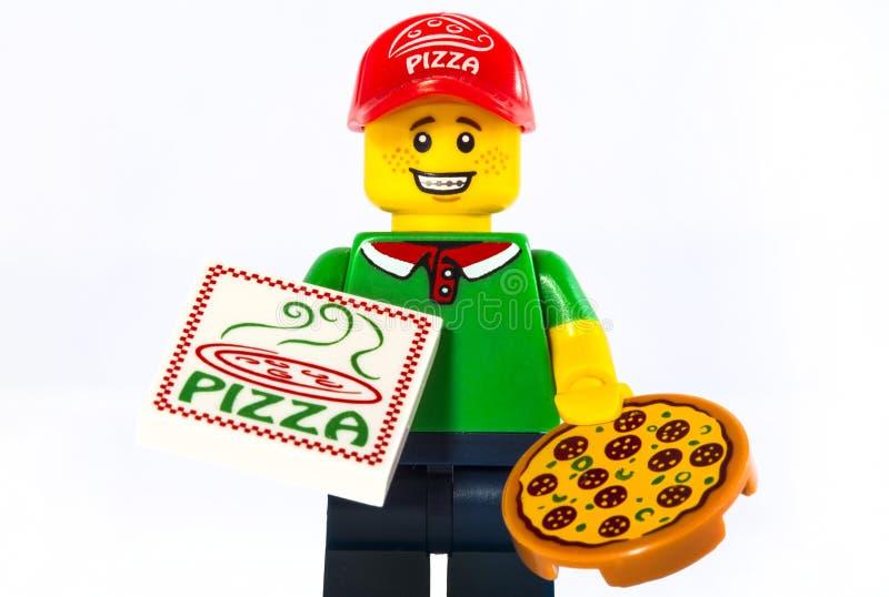 Vrolijke jonge bezorger die een pizzadoos houden terwijl geïsoleerd op wit royalty-vrije stock fotografie