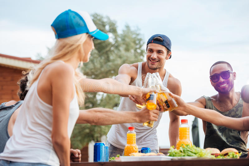Vrolijke jonge bier drinken en vrienden die in openlucht vieren stock foto