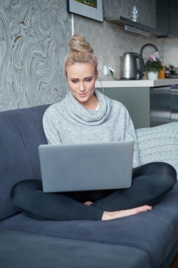 Vrolijke jonge blonde vrouwenzitting op laag in woonkamer en het gebruiken van laptop stock afbeelding