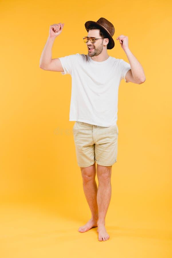 vrolijke jonge blootvoetse mens die in borrels en zonnebril weg kijken royalty-vrije stock fotografie