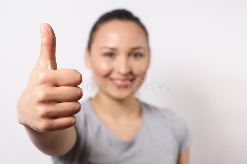 Vrolijke jonge dame die duimen tonen en camera bekijken Mooie vrouw die iets adviseren Aanbevelingsconcept, voorzijde stock foto