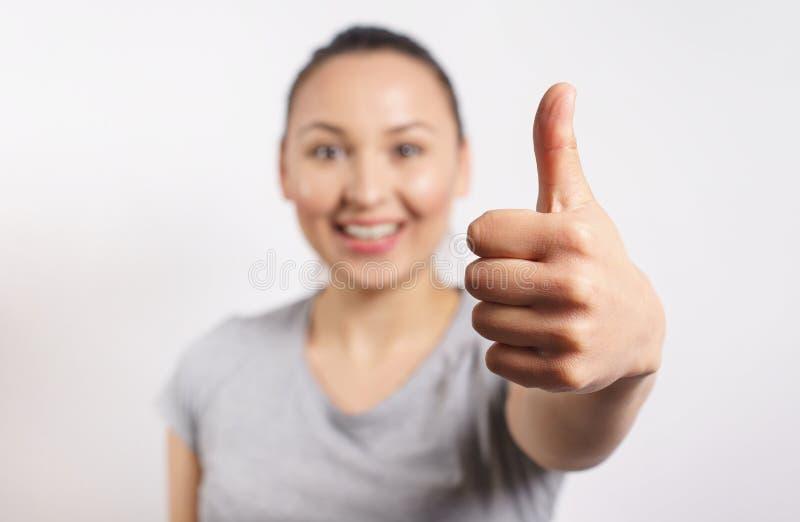 Vrolijke jonge dame die duimen tonen en camera bekijken Mooie vrouw die iets adviseren Aanbevelingsconcept, voorzijde stock fotografie