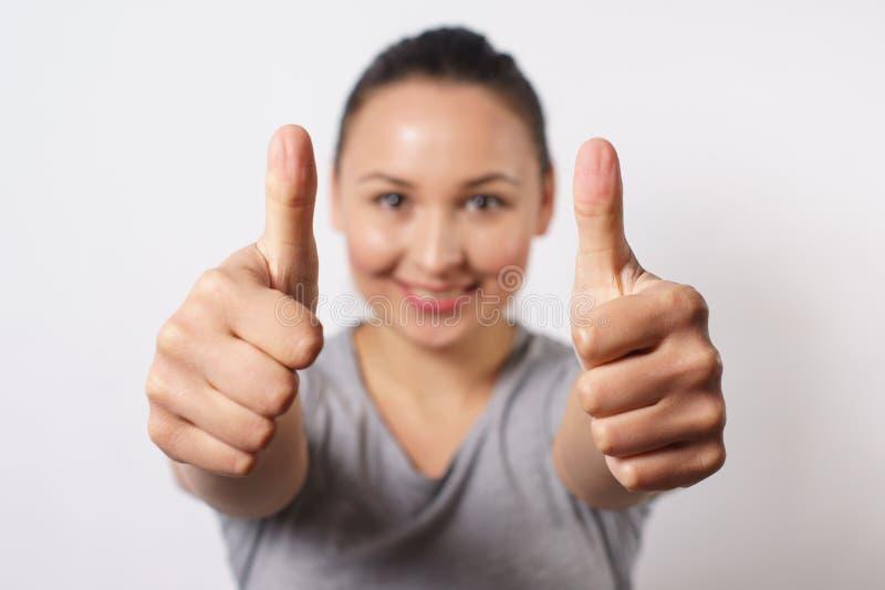 Vrolijke jonge dame die twee duimen tonen en camera bekijken Mooie vrouw die iets adviseren Aanbevelingsconcept, royalty-vrije stock foto