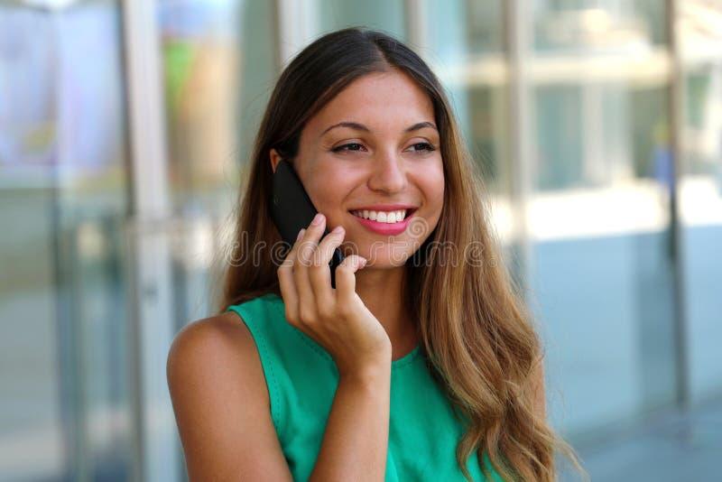 Vrolijke jonge dame die zich dichtbij glasmuur die bevinden van winkelcentrum telefonisch spreken Vrij jong meisje die met slimme royalty-vrije stock foto's