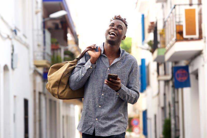 Vrolijke jonge de holdingshandtas die van de afro Amerikaanse kerel buiten met mobiele telefoon lopen royalty-vrije stock foto