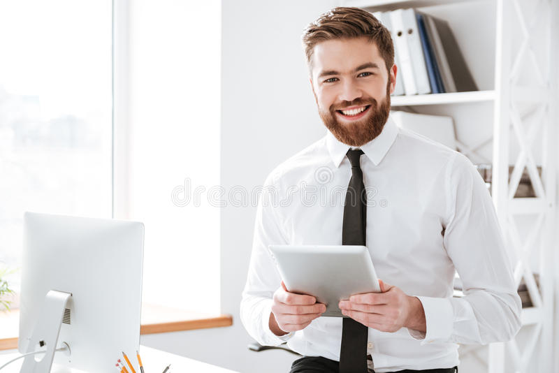 Vrolijke jonge de tabletcomputer van de zakenmanholding in handen royalty-vrije stock foto