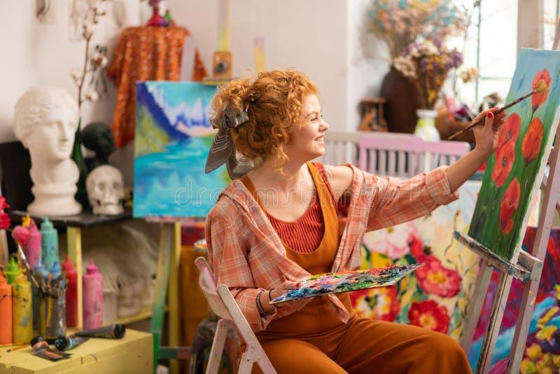 Vrolijke jonge kunstenaar die het gelukkige het genieten van schilderen voelen royalty-vrije stock afbeelding