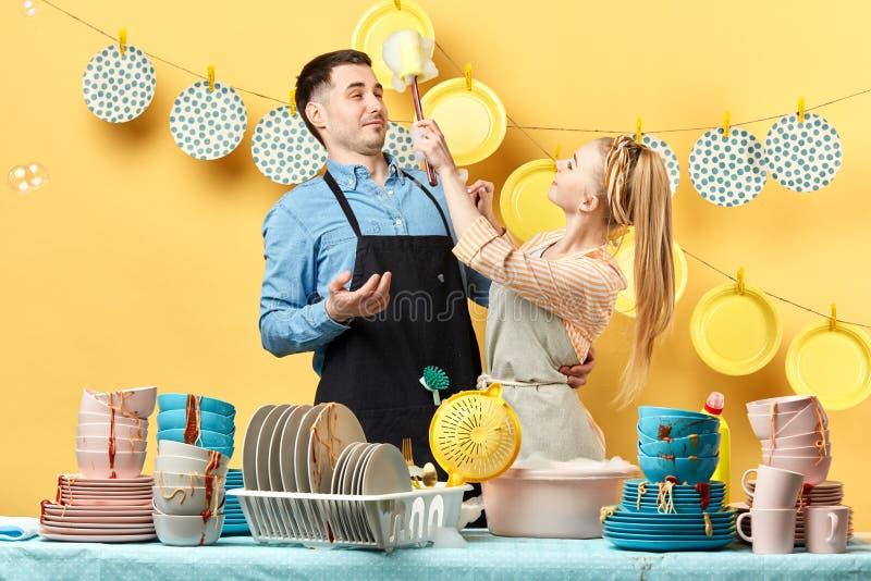 Vrolijke jonge man en vrouw die schuimpartij in de keuken hebben stock foto