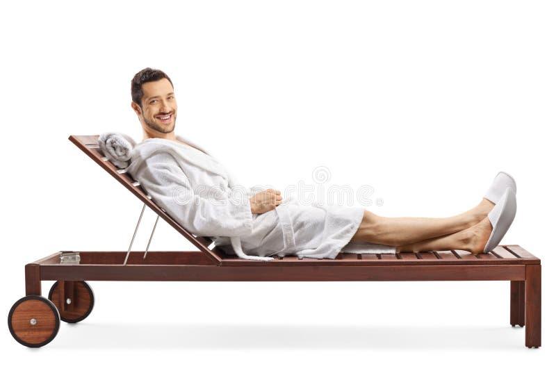 Vrolijke jonge mens in badjas het ontspannen op een zitkamerstoel en het glimlachen bij de camera royalty-vrije stock afbeelding