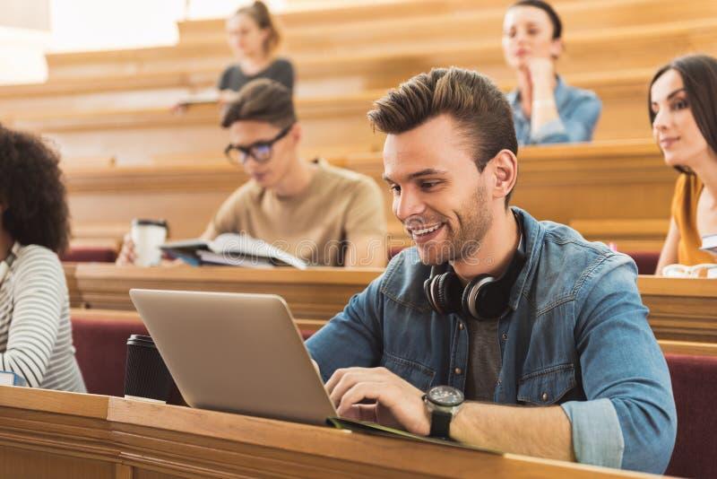 Vrolijke jonge mens die met computer bij universiteit bestuderen stock fotografie
