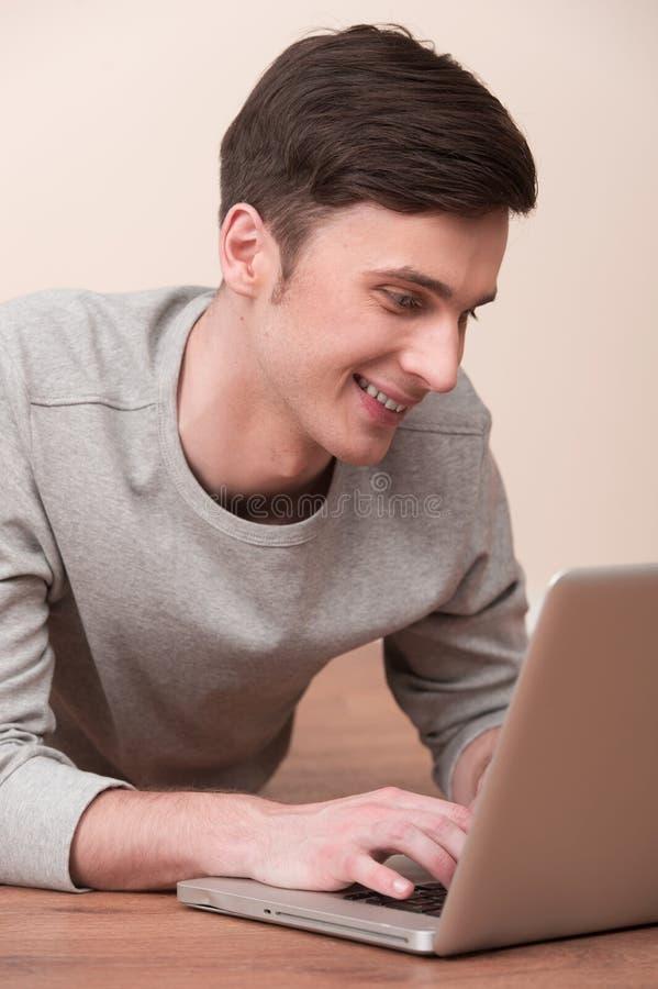 Vrolijke jonge mens die op vloer met laptop liggen royalty-vrije stock afbeelding