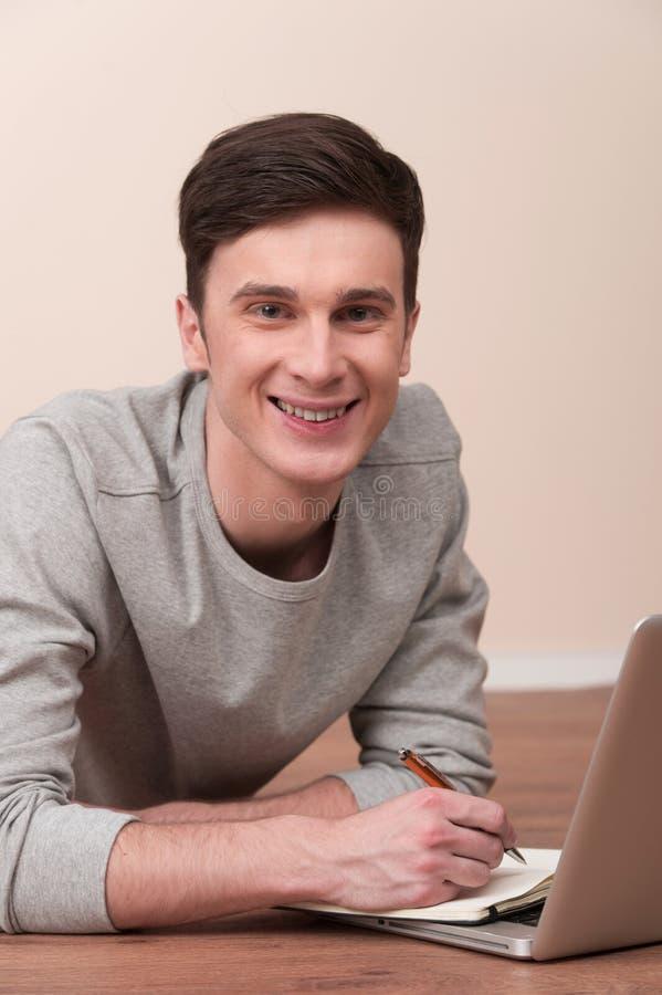 Vrolijke jonge mens die op vloer met laptop liggen royalty-vrije stock fotografie