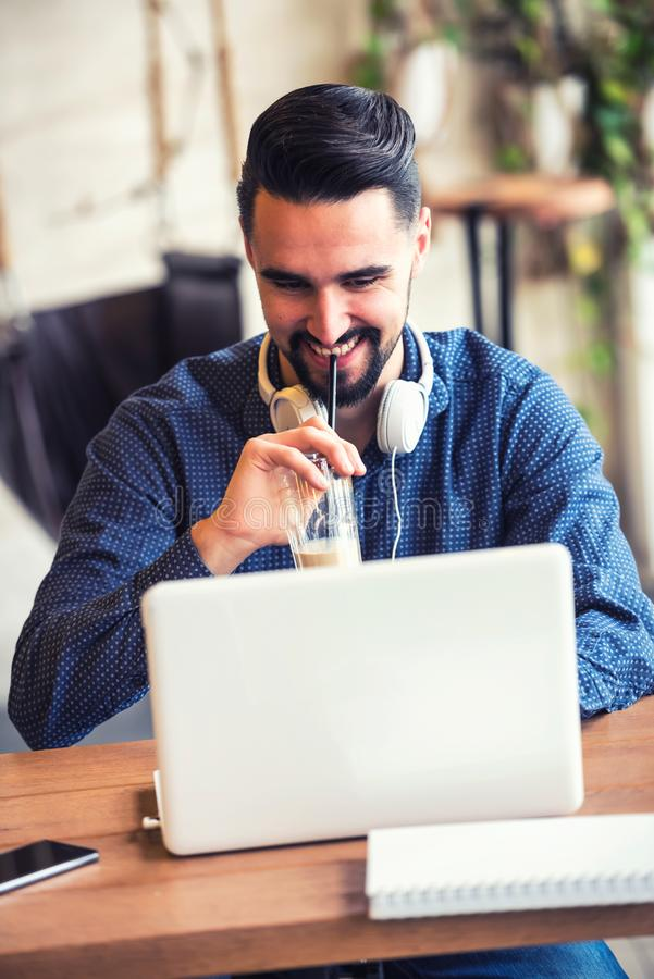 Vrolijke Jonge Mens met Baard die aan Laptop in Koffiewinkel werken royalty-vrije stock afbeeldingen