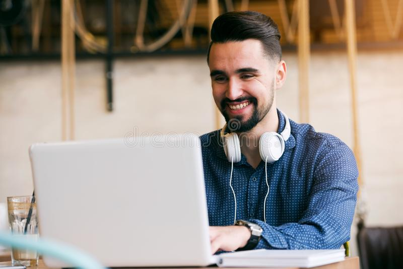 Vrolijke Jonge Mens met Baard die aan Laptop in Koffiewinkel werken stock afbeelding