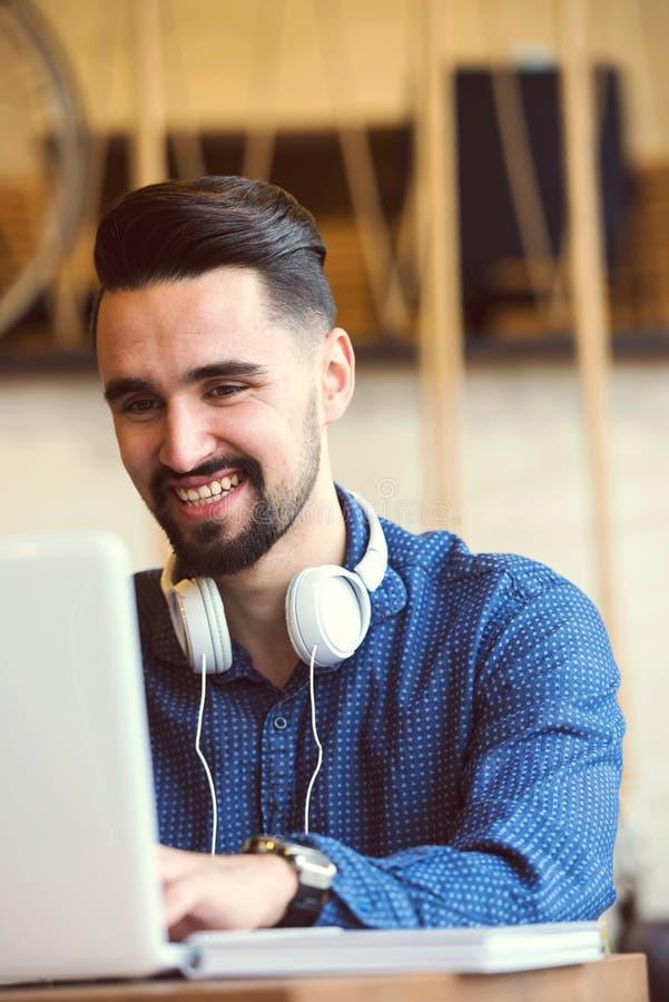 Vrolijke Jonge Mens met Baard die aan Laptop in Koffiewinkel werken royalty-vrije stock foto's