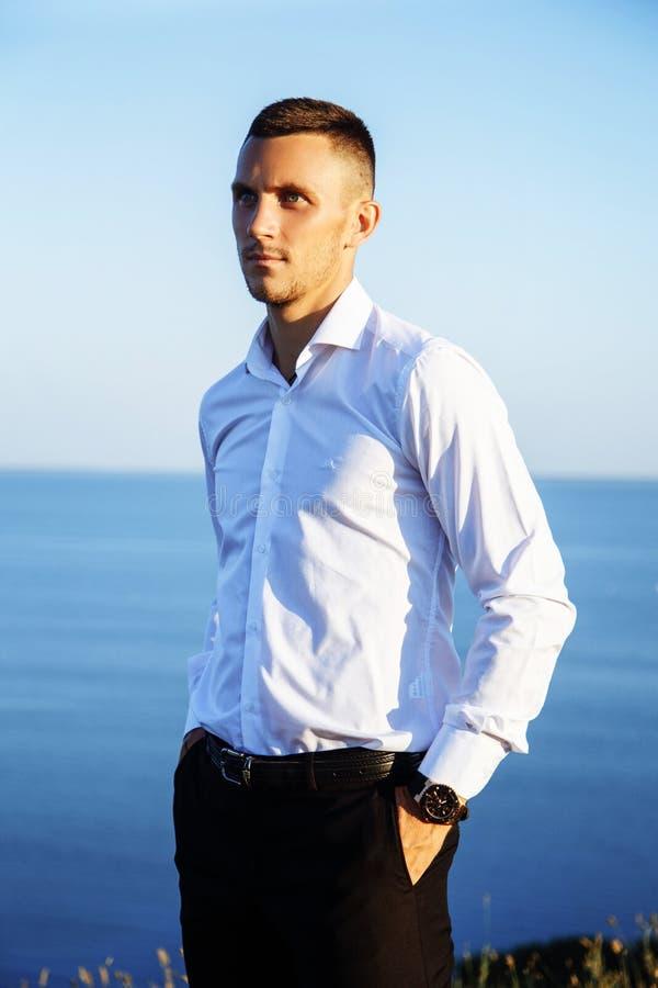 Vrolijke jonge mens in wit overhemd die zich dichtbij het overzees bevinden royalty-vrije stock foto's