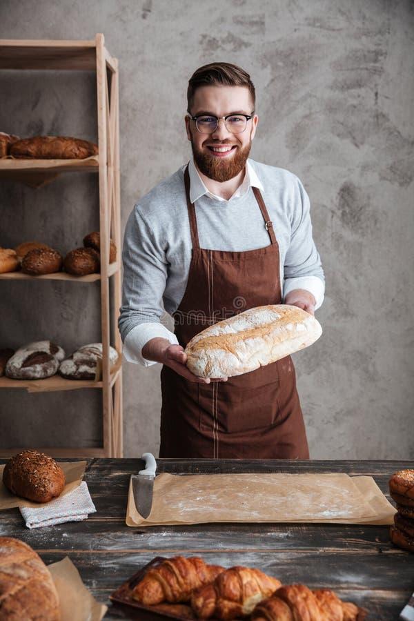 Vrolijke jonge mensenbakker die zich bij het brood van de bakkerijholding bevinden stock foto