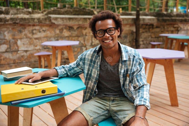 Vrolijke jonge mensenzitting en het glimlachen in openluchtkoffie royalty-vrije stock afbeelding