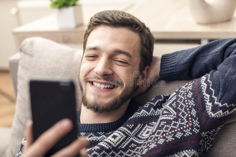 Vrolijke jonge mobiele telefoon houden en mens die thuis glimlachen stock afbeelding