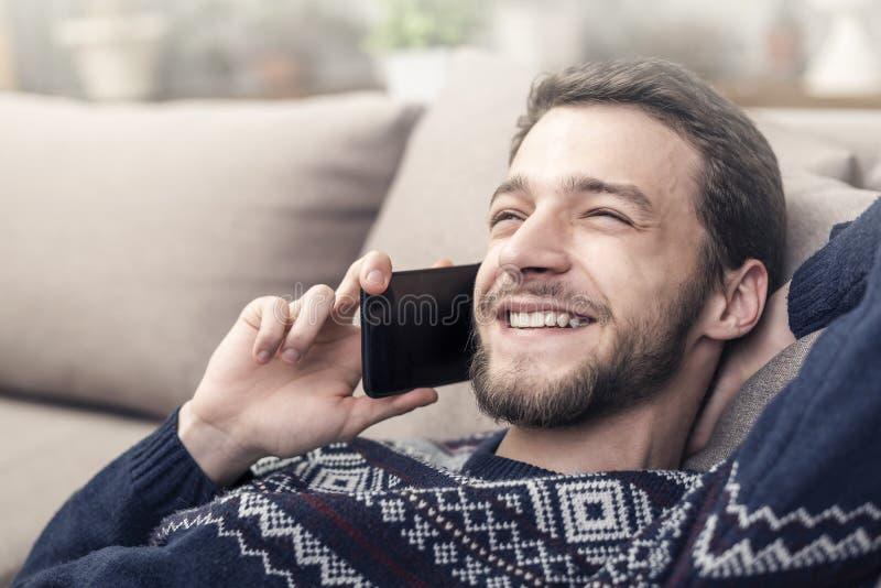 Vrolijke jonge mobiele telefoon houden en mens die thuis glimlachen royalty-vrije stock afbeeldingen