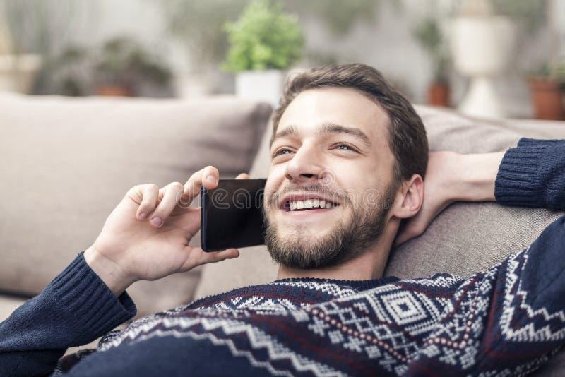 Vrolijke jonge mobiele telefoon houden en mens die thuis glimlachen royalty-vrije stock foto