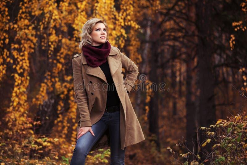 Vrolijke jonge modevrouw die in het herfstpark loopt stock foto's